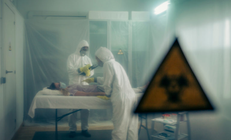 Doctors standing over infected person in protective medical suits.