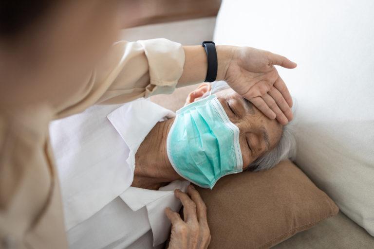 Asian man with flu like symptoms wearing a mask.